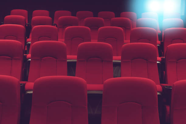 movie theater empty auditorium with red seats and blue lighting stock photo