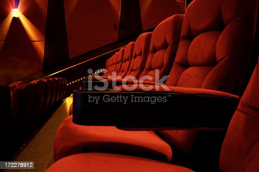 A row of bright red, brand new movie theater stadium seats.