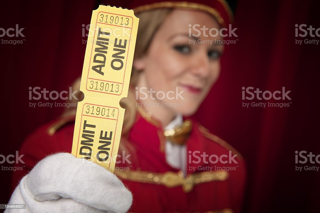 Movie theater usher holding tickets that says ADMIT ONE stock photo