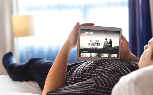 Movie, video and online streaming service in tablet. Man choosing and watching digital film with smart device. Person relaxing. Tv network internet site on screen. stock photo