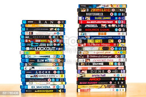 Huntly, Scotland - May 17, 2016: Two separate stacks of Bluray and DVD films on a wooden table against a pure white backdrop. The Bluray movies are on the left, the DVDs are on the right, and consist of films from the 1950's to the present day.