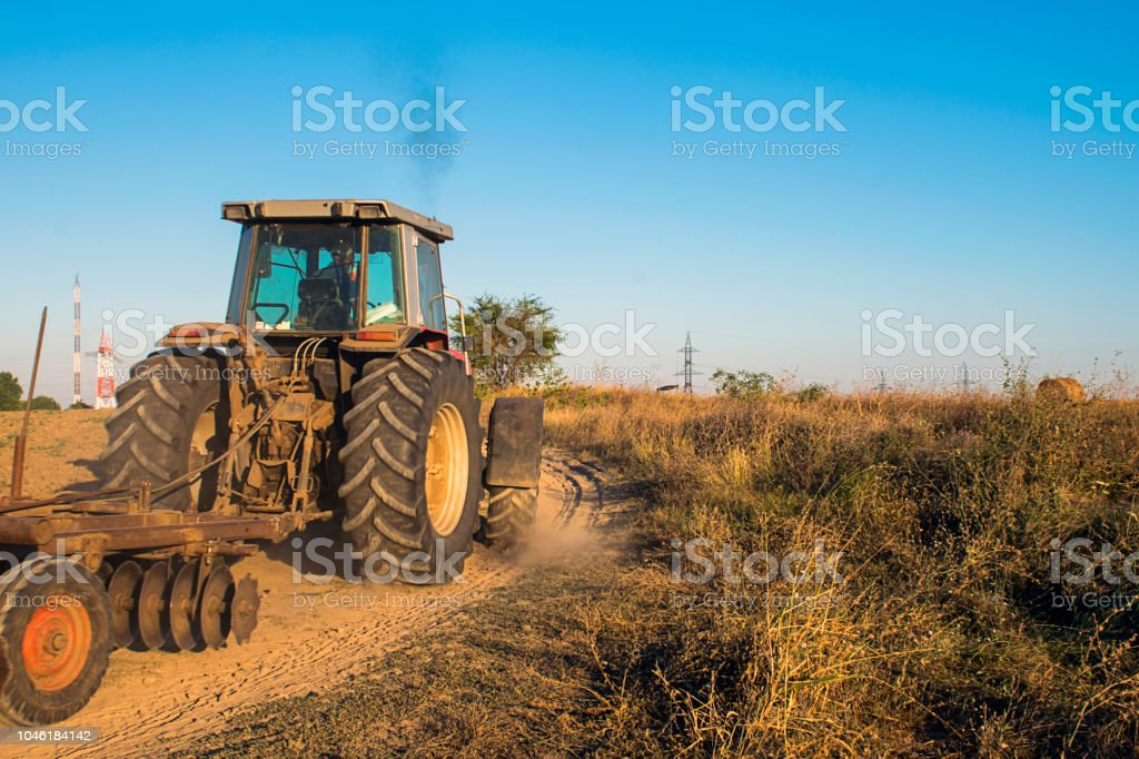 Moving Agriculture Tractor On A Dirt Road Stock Photo & More