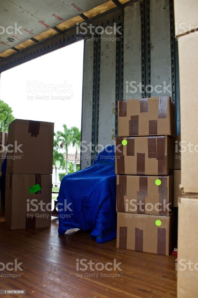 Moving van interior with packed boxes by open door with bright...
