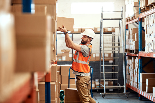 Shot of a young man working in a warehouse