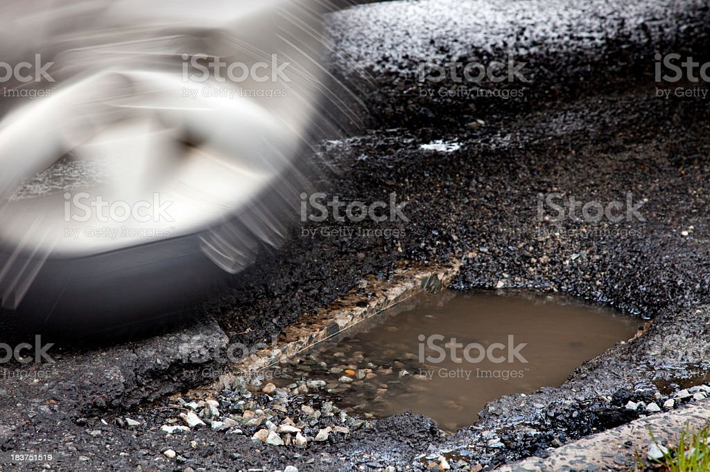 Moving auto tire about to enter large pothole, Motion blur stock photo