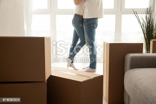 938682826istockphoto Moving boxes with couple embracing at background, close up view 916092524