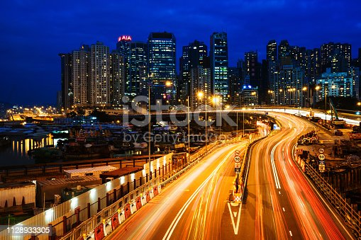 860696690 istock photo Moving car with blur light through city at night 1128933305