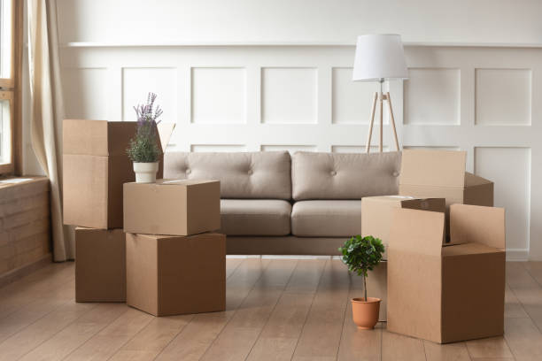 Moving day concept, cardboard boxes in modern house living room Moving day concept, cardboard carton boxes stack with household belongings in modern house living room, packed containers on floor in new home, relocation, renovation, removals and delivery service physical activity stock pictures, royalty-free photos & images