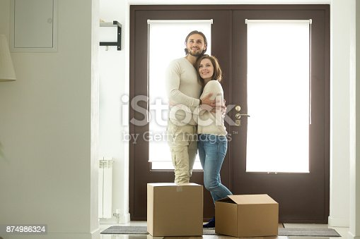 938682826istockphoto Moving day concept, excited couple homeowners embracing in new home 874986324