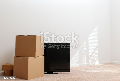 Empty living room with moving boxes and television.  Please see my portfolio for other home improvement and moving images.