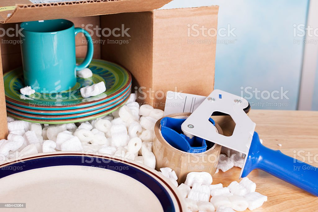 Relocation, moving concept. Dishes, plates, cup packed inside a...