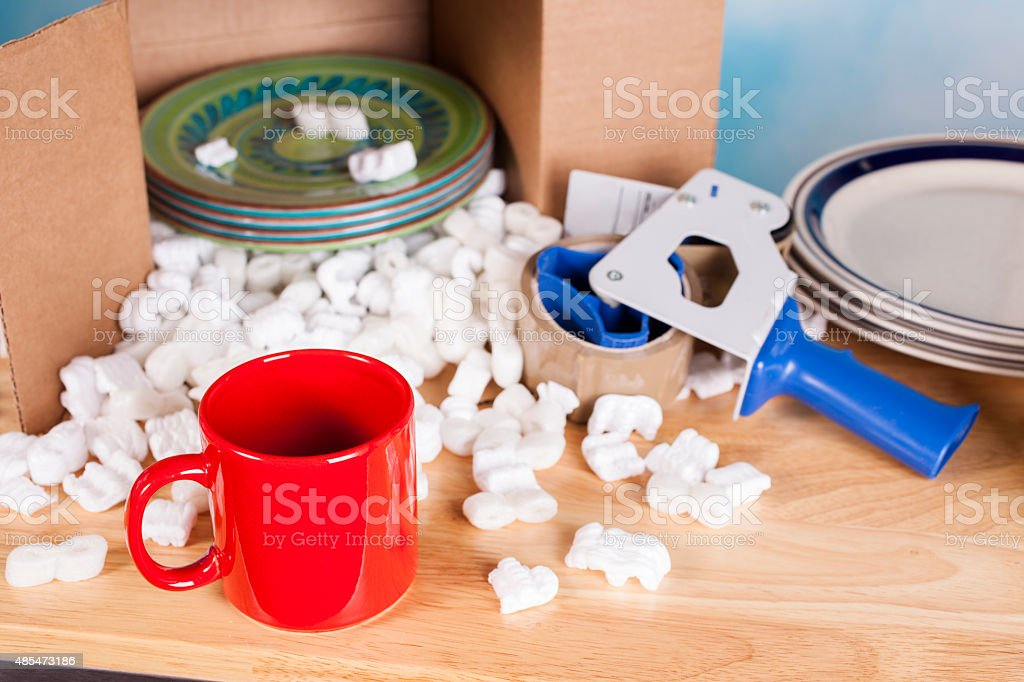 Relocation, moving concept. Plates packed inside a cardboard box with...