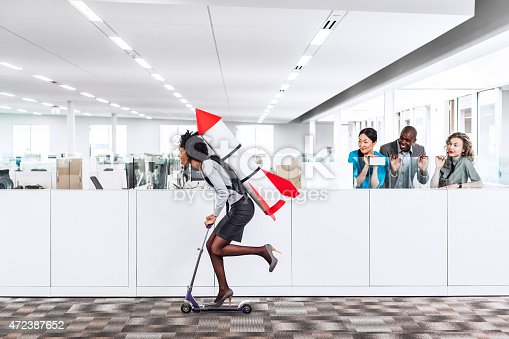Woman speeding thru the office on the scooter with a rocket strapped to her back while her happy multiethnic  co-workers are watching her succeed in the workplace. Plenty of copyspace.