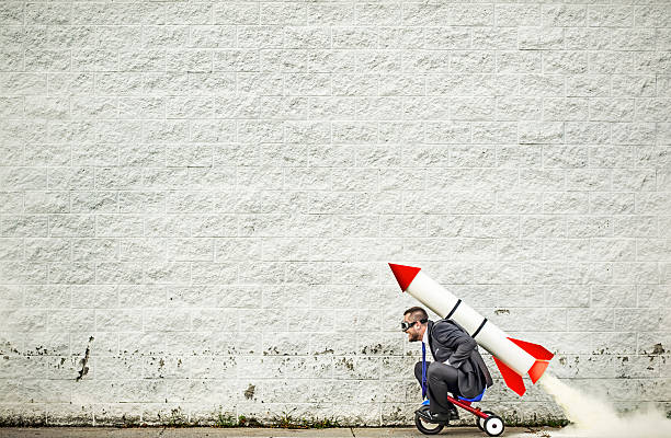 Moving forward Businessman riding a tricycle and getting help from the rocket strapped to his back :-) speed stock pictures, royalty-free photos & images