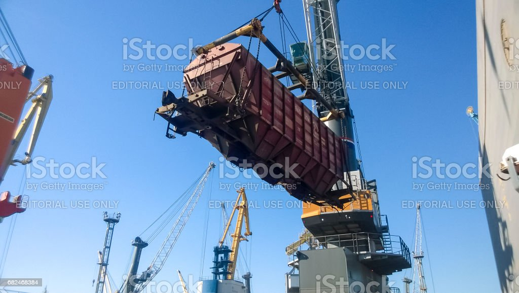 Moving freight railway car in the port by a port crane. Cargo lifting operations. Industrial port. stock photo