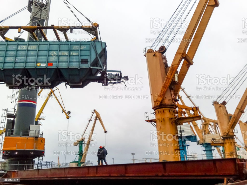 Moving freight railway car in the port by a port crane. Cargo lifting...