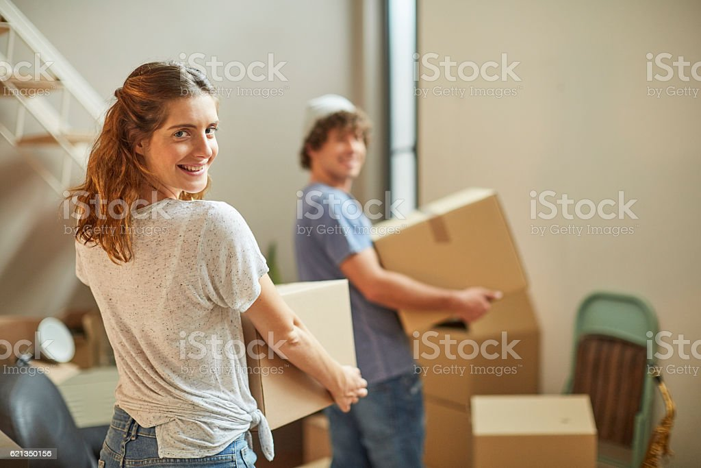 Moving home new beginnings.  Couple carrying boxes. - foto de acervo