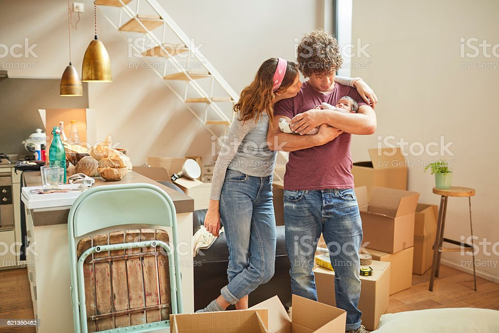 Moving home new beginnings. Couple with baby. stock photo