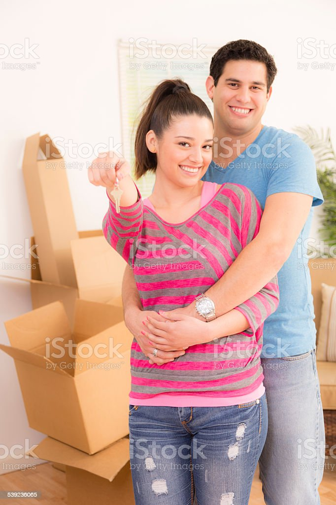 Moving, Homes: Latin descent couple shows off key. New house. royalty-free stock photo