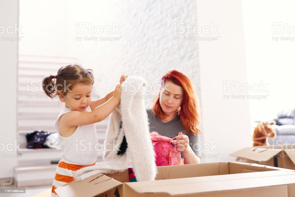 Mother with her little girl arranging clothes from cardboard boxes
