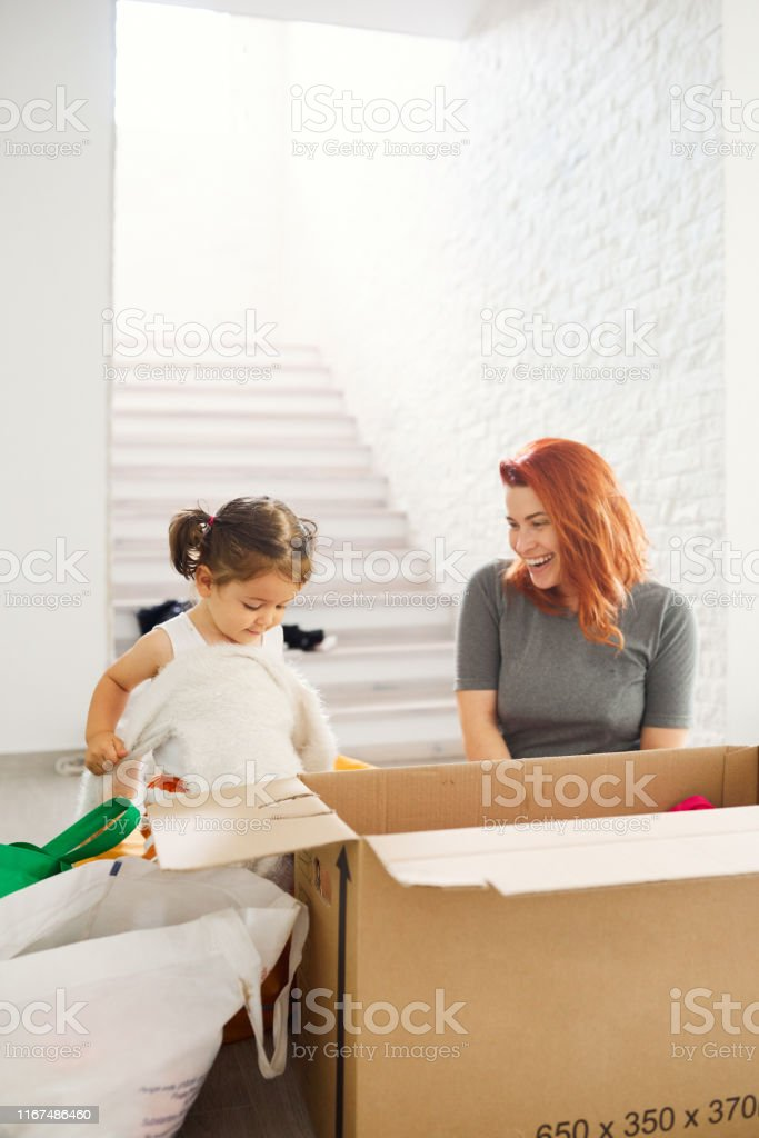 Little girl helping her mother to unpack clothes