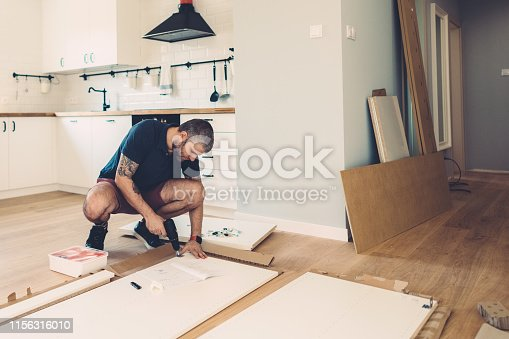 Mid adult man assembling wardrobe for his new home