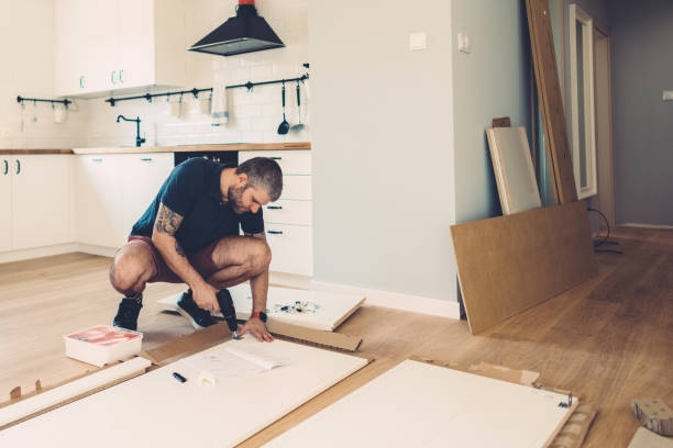 Moving house concept Mid adult man assembling wardrobe for his new home diy stock pictures, royalty-free photos & images