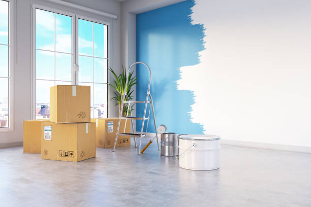 Moving House Concept with Cardboard Boxes and Wall Painting stock photo