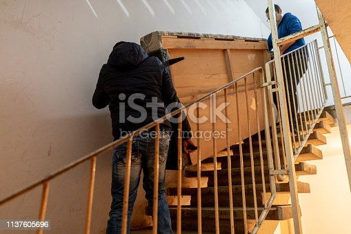 Two young men are carrying heavy furniture downstairs