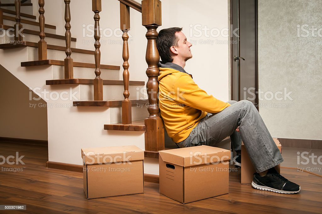 Moving house. Young man with cardboard boxes on a stairs. stock photo