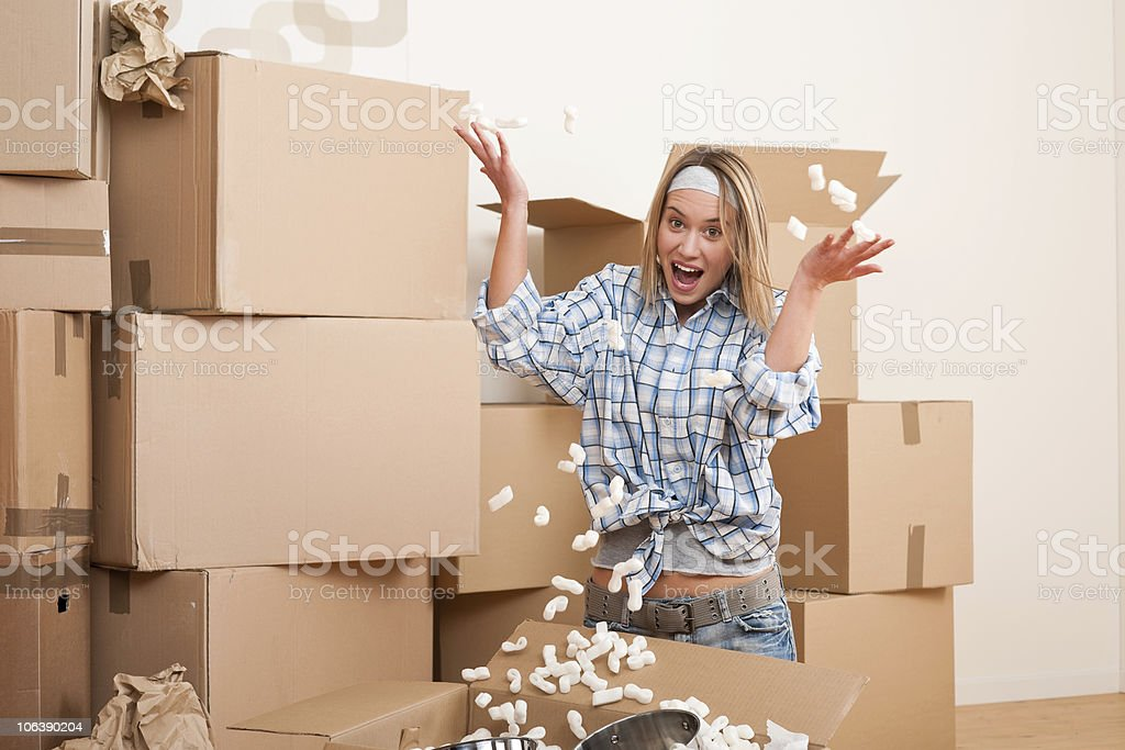 Moving house: Young woman having fun royalty-free stock photo