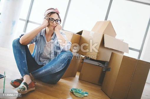 Young woman sitting on the floor, tired of all the work that she done by herself at her apartment.