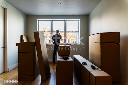 Moving in! The mature Caucasian man talking by phone nearby the window in the empty living room filled with cardboard boxes in the recently rented apartment. Brooklyn, New York, USA.