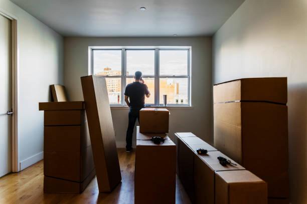 Bewegung! Die Reife kaukasischen Mann sprechen per Telefon in der Nähe der Fenster in das leere Wohnzimmer voller Kartons im neuen Haus. – Foto