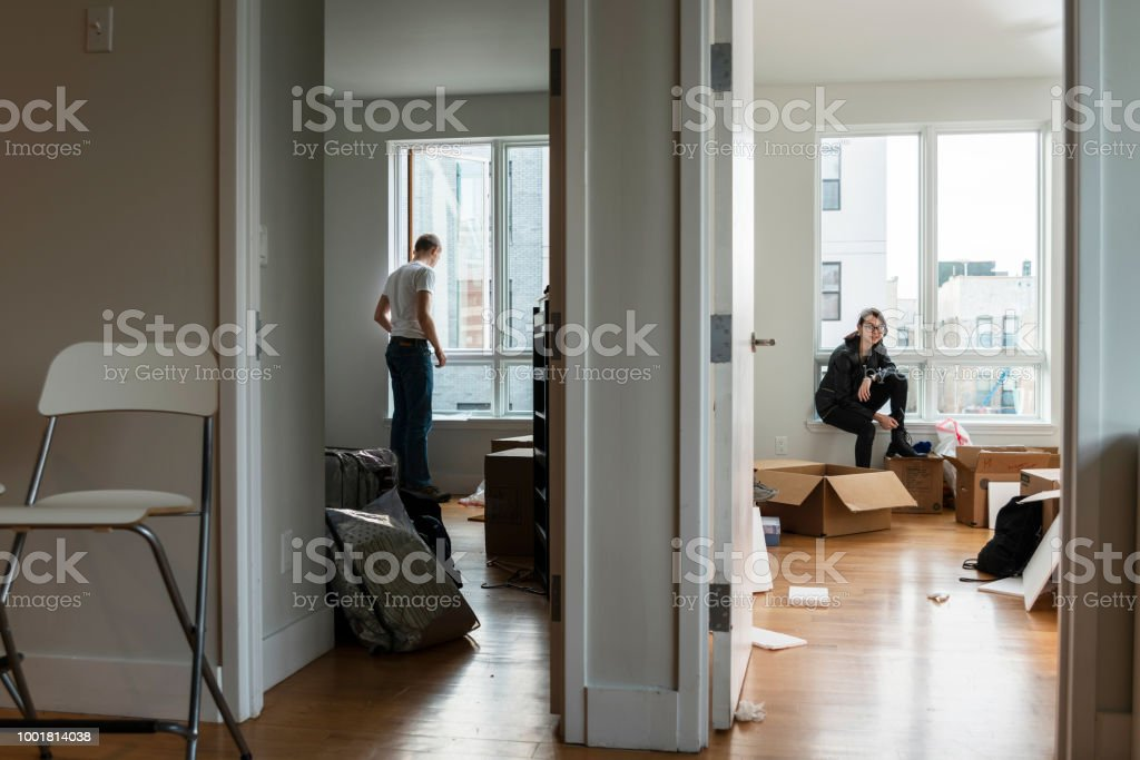 Moving into the new house. Teenage girl sitting in her future room between boxes with her stuff, and the young 28-years-old man looking around the apartment - foto stock