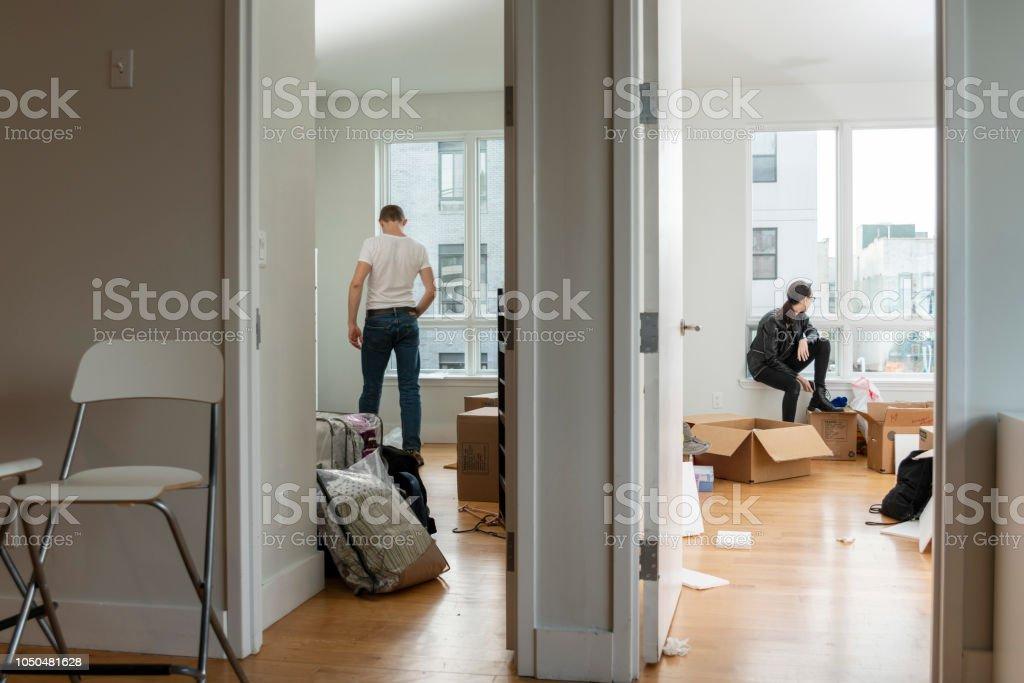 Déménagement dans la nouvelle maison. Adolescente, assis dans sa future chambre entre boîtes avec ses trucs et le jeune homme de 28 ans à la recherche autour de l'appartement - Photo