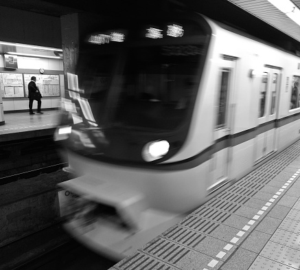 Brisbane, Australia - December 12, 2016: Scene of a moving locomotive train arriving to the Brisbane Central station in black and white. The station is located in Brisbane, which is the capital city of Queensland state in Australia. There is a passenger stands on the platform. The photo is taken in the afternoon.