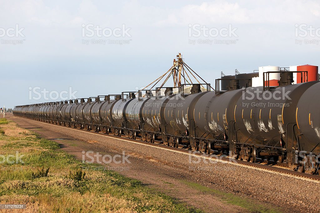Moving oil pipeline - railroad cars passing industrial site stock photo