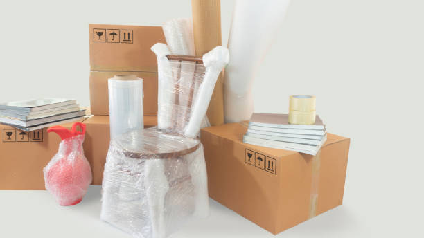 Moving scene with a chair and vase packed in plastic bubble with closed cardboard boxes, books and rolls of plastic and foam to pack Moving scene with a chair and vase packed in plastic bubble with closed cardboard boxes, books and rolls of plastic and foam to pack on white background alejomiranda stock pictures, royalty-free photos & images