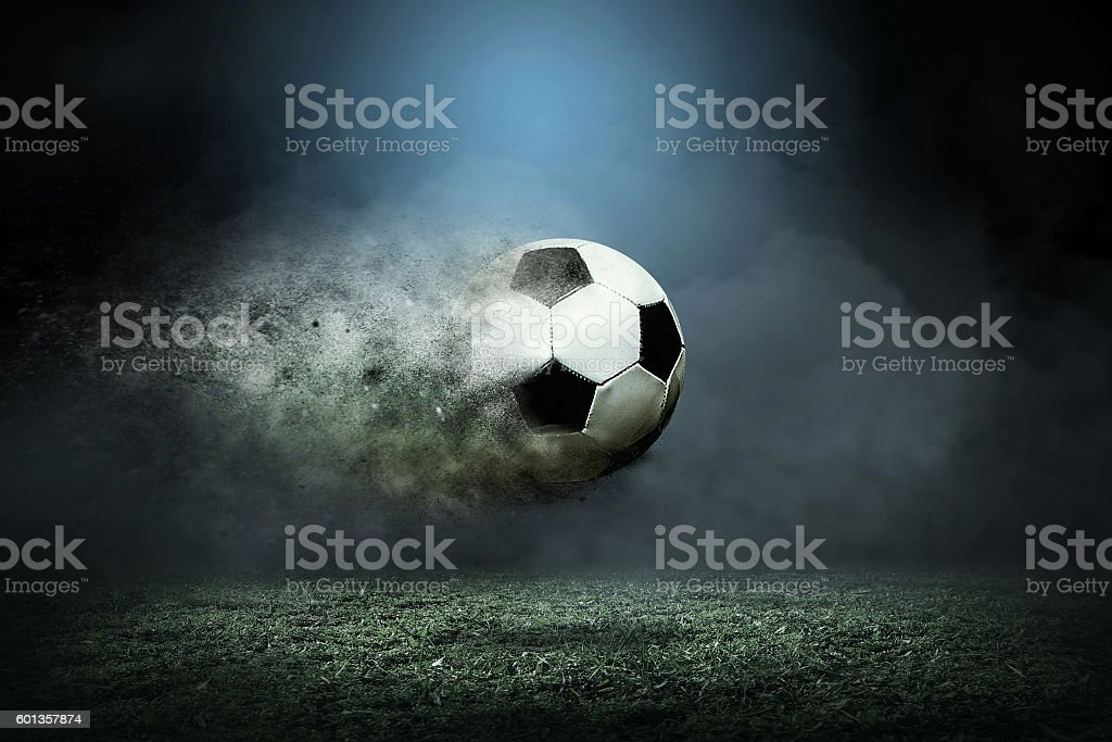 Moving soccer ball around splash drops on the stadium field. stock photo