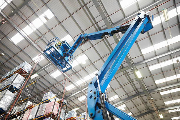 moving stock in a warehouse with a cherry picker, low angle - skylift bildbanksfoton och bilder