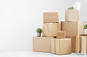 istock Moving to a new home. Belongings in cardboard boxes, books and green plants in pots stand on the gray floor against the background of a white wall. 1135246997