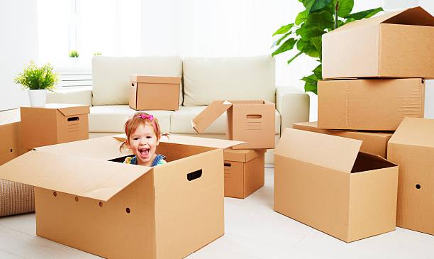 umzug zum neuen apartment. glückliches kind in cardboard box - kinder verpackung stock-fotos und bilder