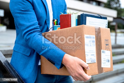Box of personal stuff in male hands, dismissed from the job or relocating to new business