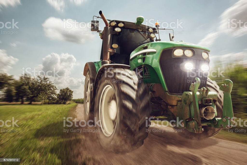 Moving Tractor on a dirt road stock photo