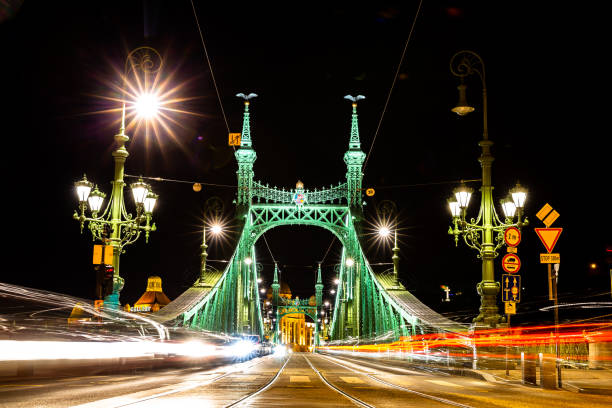 Moving Trams on Liberty Bridge, Budapest This pics shows moving tram on liberty bridge in Budapest at night time.The pic shows light trail of tram when it pass over liberty bridge and its taken in January 2019. liberty bridge budapest stock pictures, royalty-free photos & images