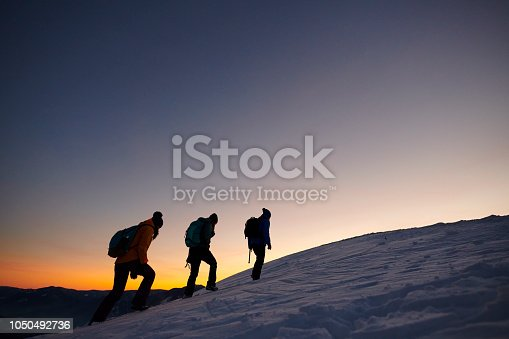 side view of three hiking friends in cold winter day moving up on the mountains.