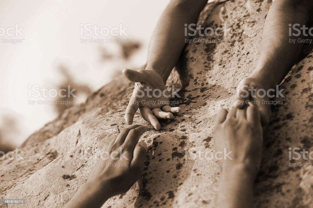A handing to help their partner in mountains.