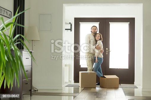 938682826istockphoto Moving with boxes concept, happy couple hugging in new home 951349642