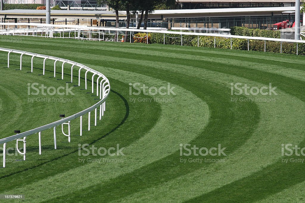 Mowed lawn used as a horse racing track restricted by fence stock photo